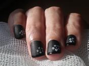Flores blancas sobre manicura francesa negro